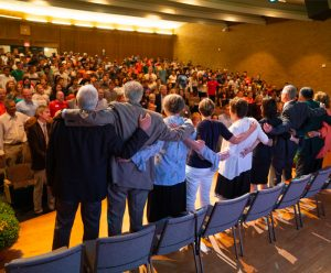 Falk faculty, staff and new students sing the Alma Mater in Grant Auditorium at the new student welcome meeting.