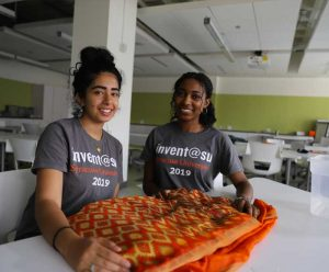 Two students pose next to a sari on a table