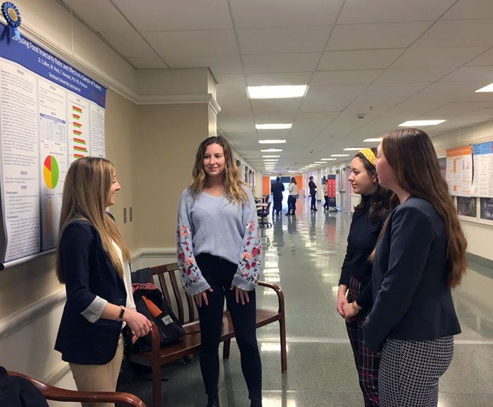 Students talk in hall in front of a winning research poster