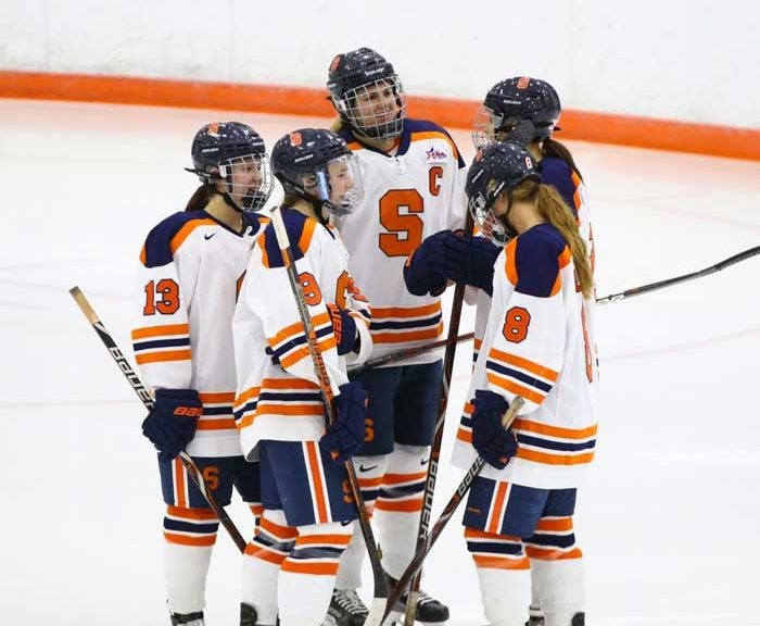 Allie Munroe and fellow hockey teammates discuss on the ice