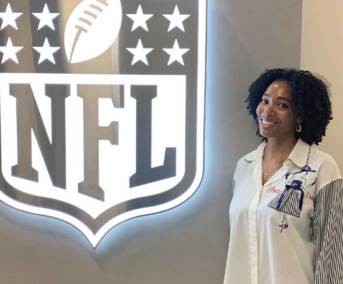 Angela Marsh-Coan poses in front of an NFL logo sign