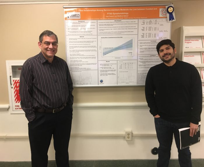 Brooks Gump and Ivan Castro stand next to a research poster