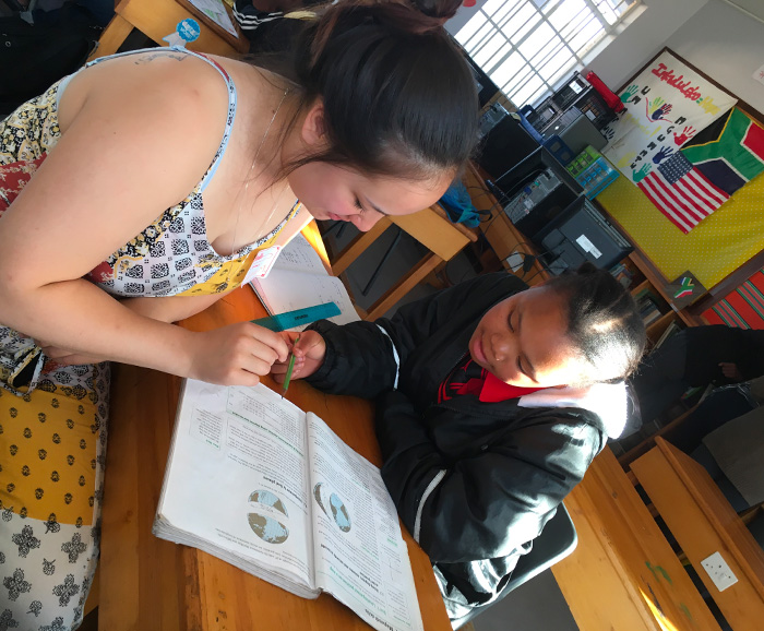 Caitlin Mogan with a student in a school classroom in South Africa