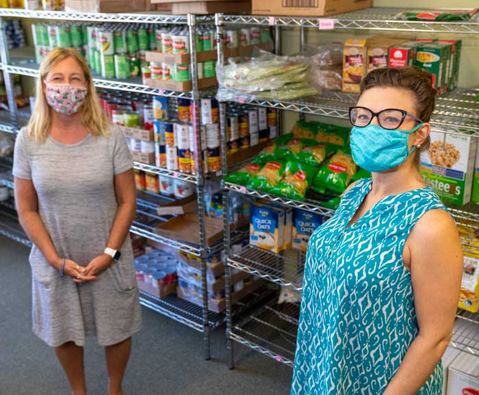 Two women stand in a food pantry isle
