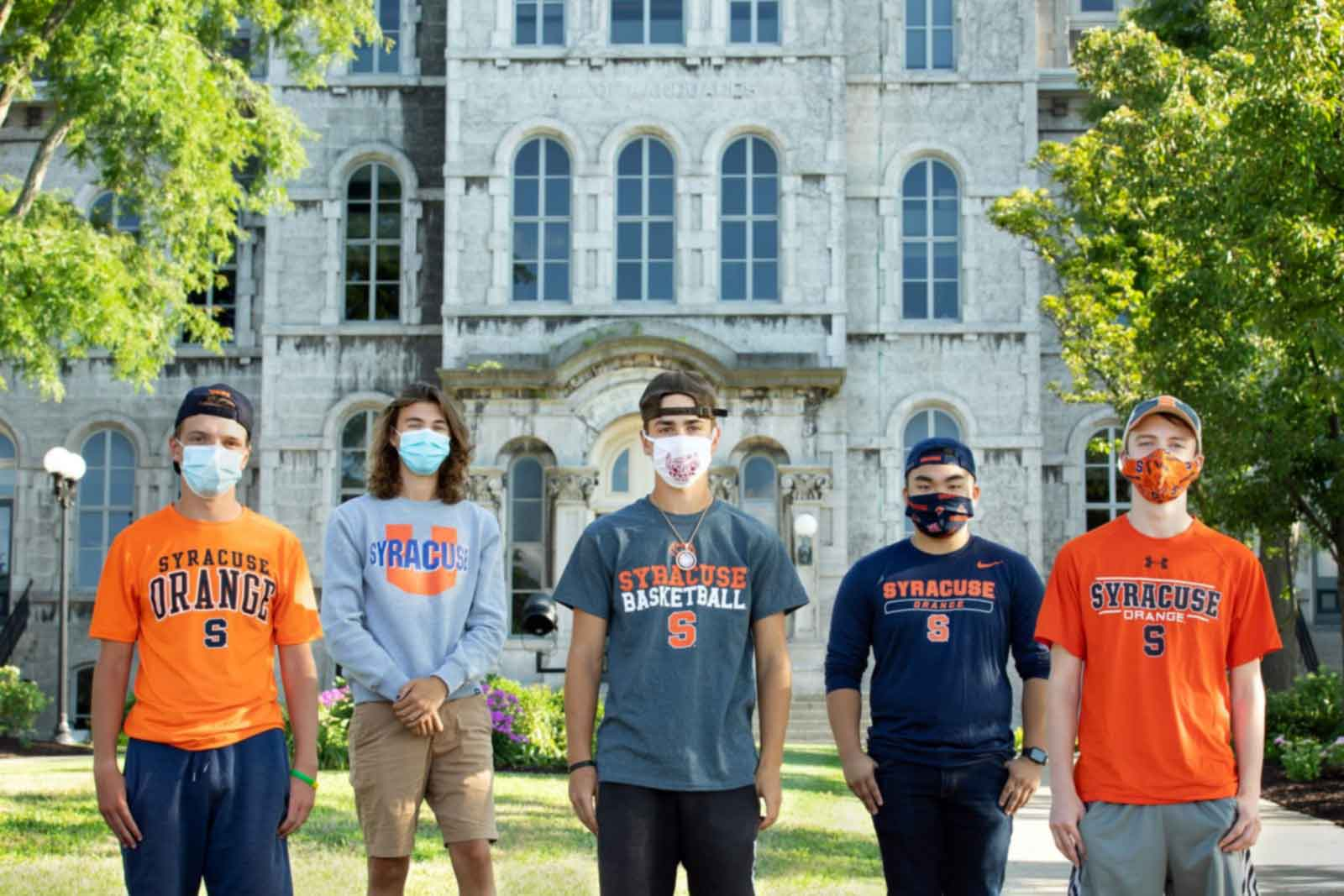 5 masked individuals are standing in front of the hall of languages