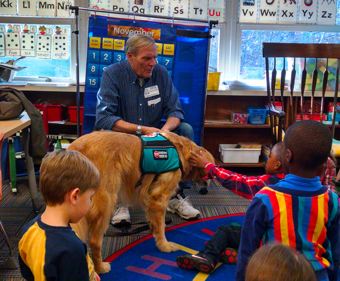 Man with dog in an elementary school classroom