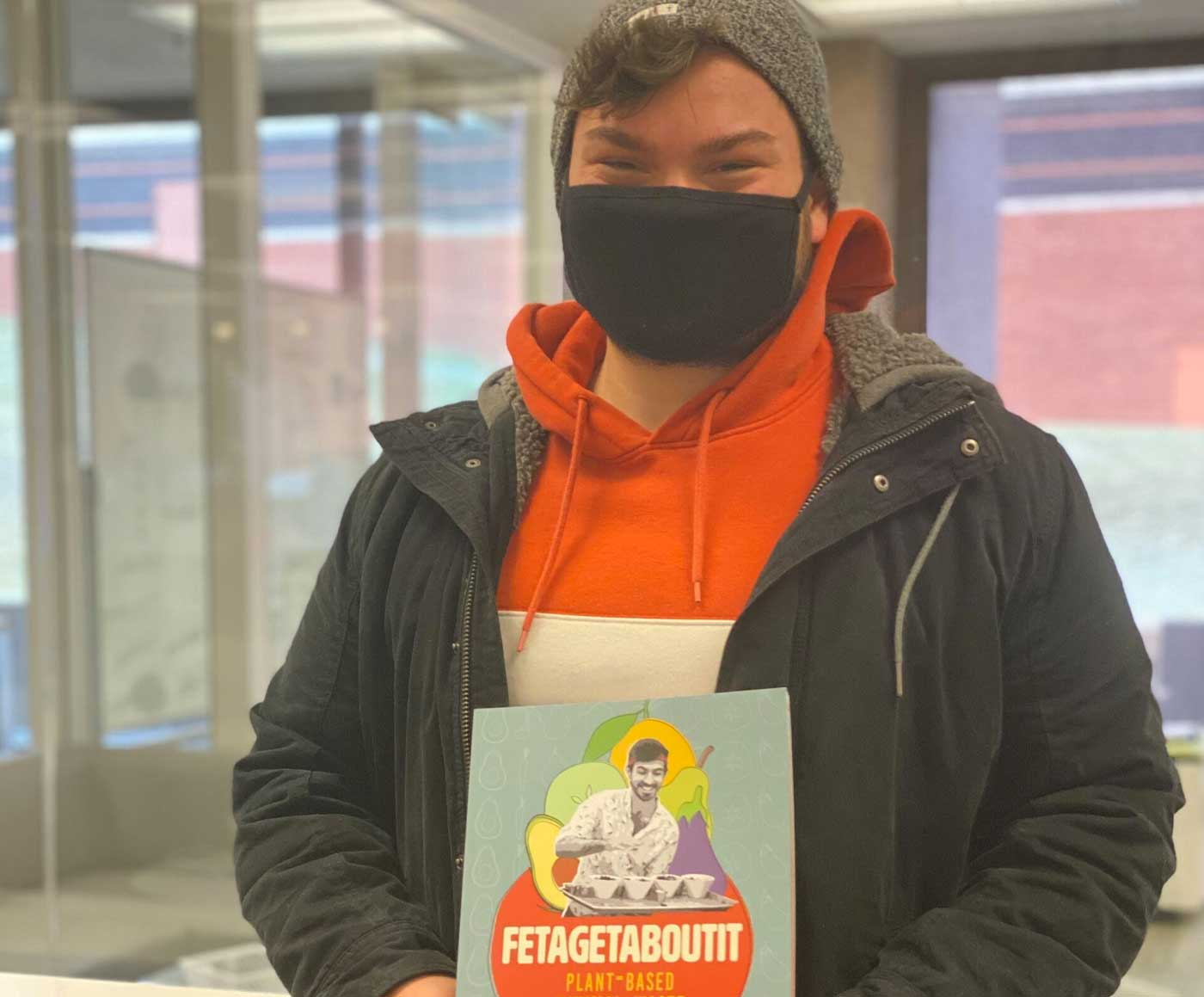 Ethan Tyo is holding the Fetagetaboutit book
