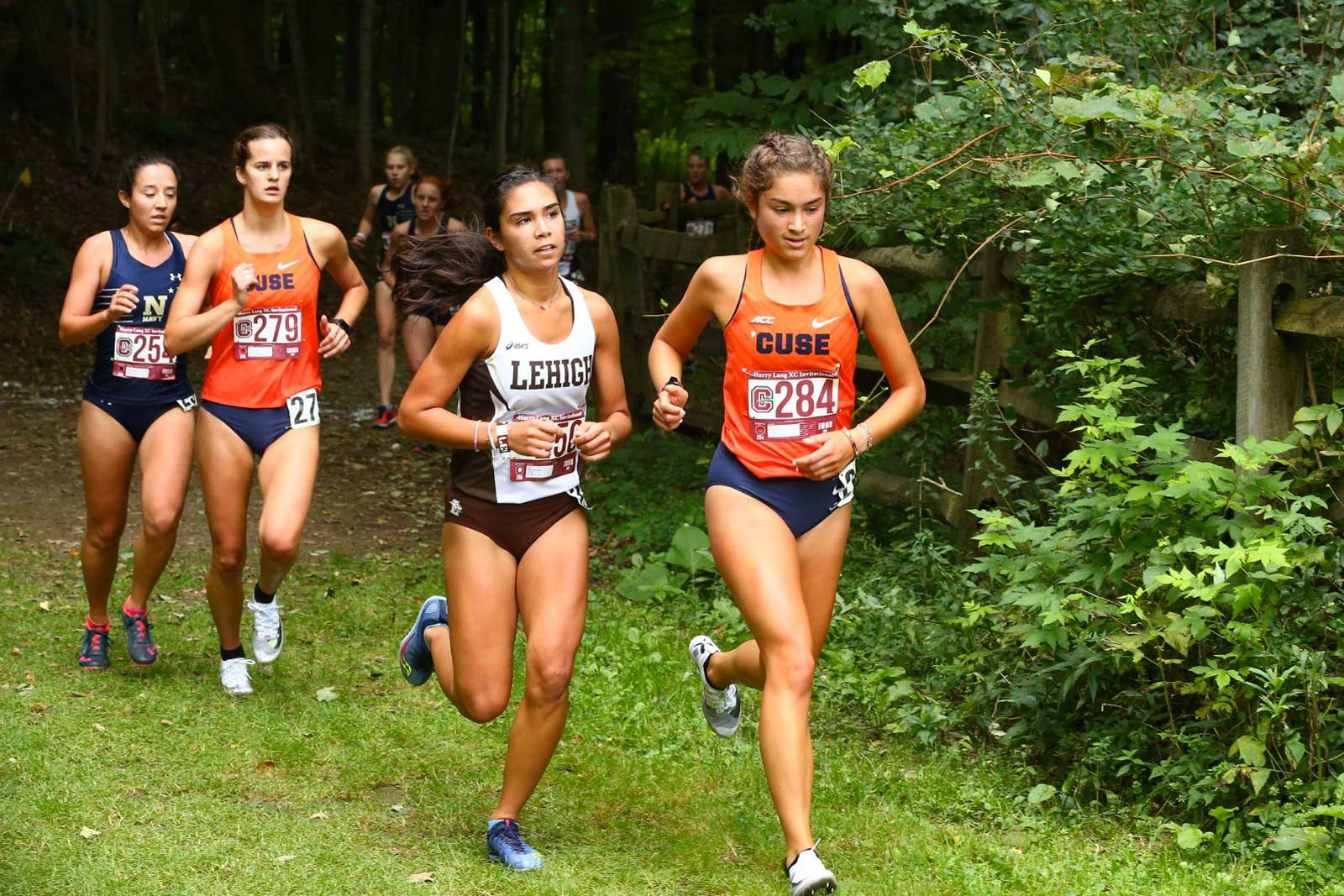 a group of female runners running out of a forest