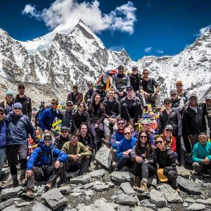 A large group of students sitting on the side of a mountain range