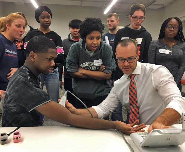Students work with a professor and monitoring equipment