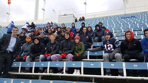 A large group of students are posed sitting in stands with winter attire