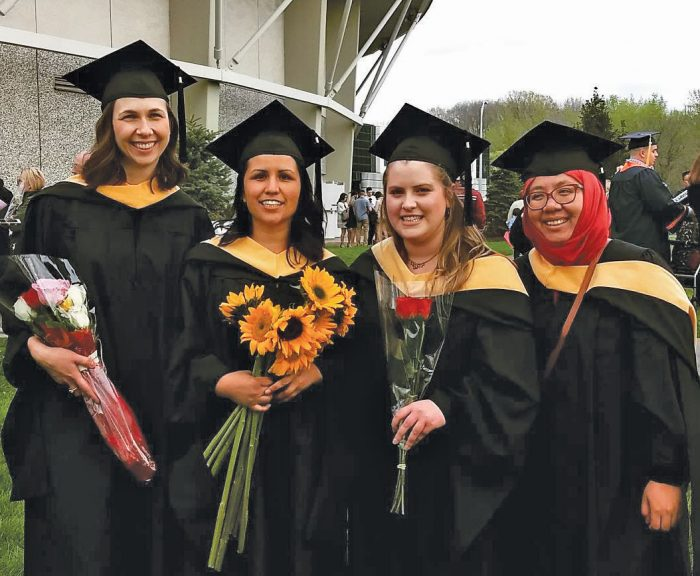 Graduates pose outside Manley Field House