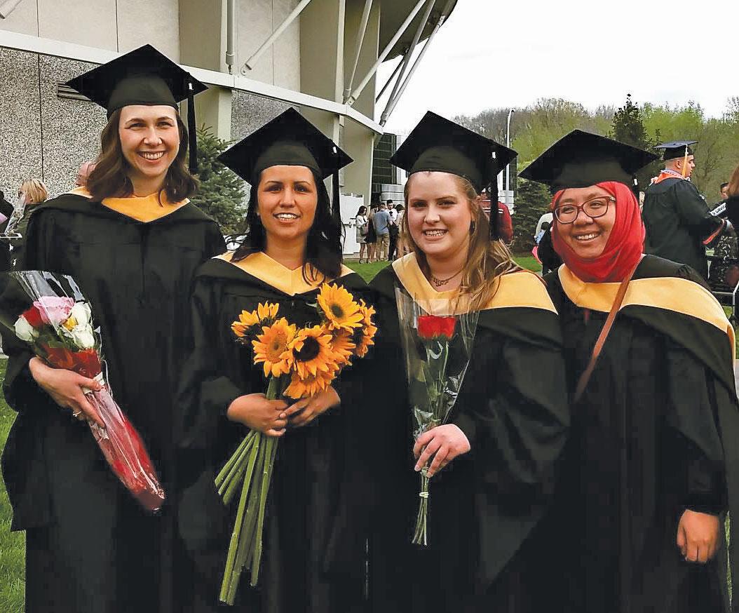 Graduates pose outside Manley Field House