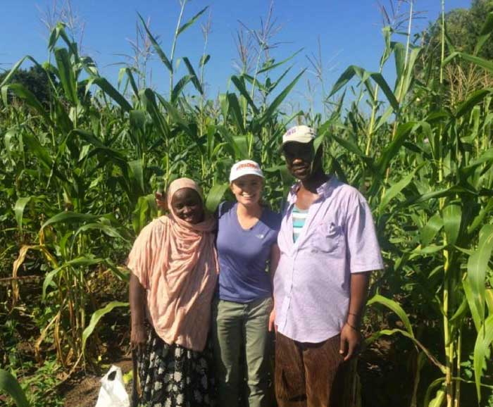 Student stands with a Somali couple in a corn field