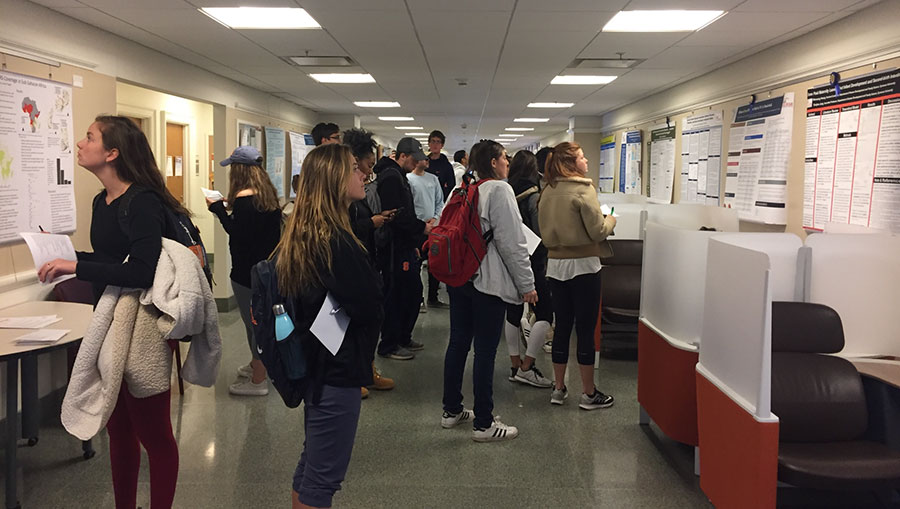 a large group of students mingle in a hallway looking at posers