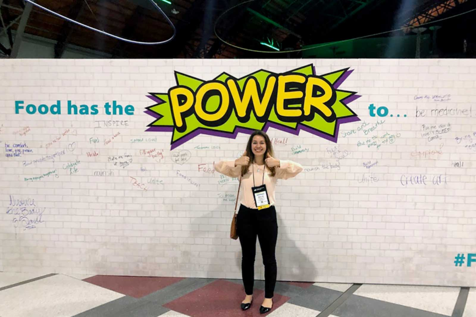 A student stands in front of a wall with writing on it.
