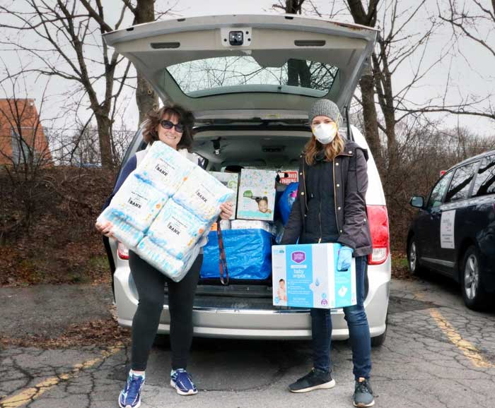 Two women are taking boxes of diapers out of the back of a car