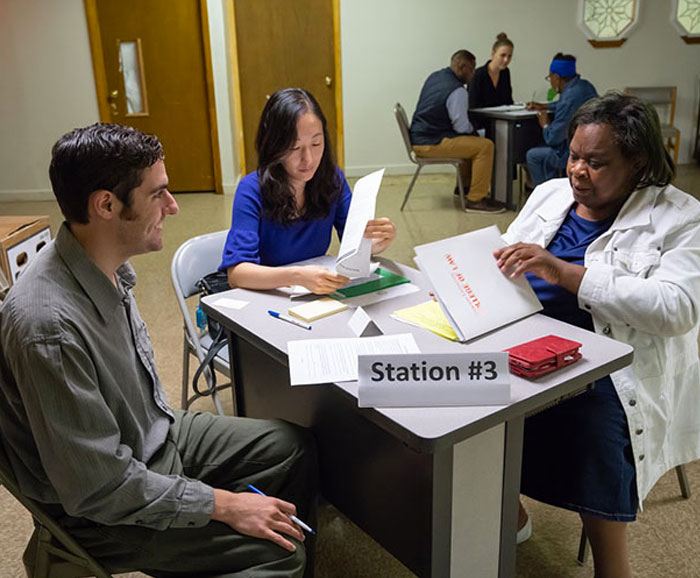 Students work with a client at a table