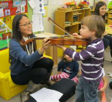 Student teaches a child to play violin