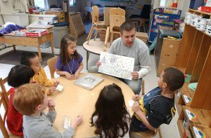 A student teaches at a table of 6 children