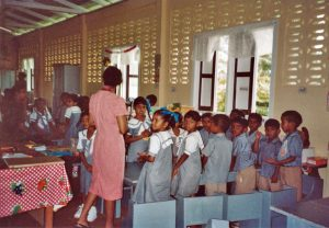 A teacher talks with students in a Caribbean classroom