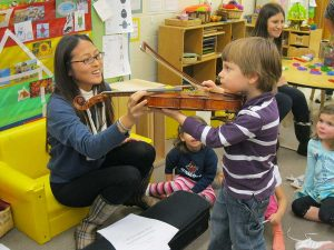 Music student gives a young child a violin lesson