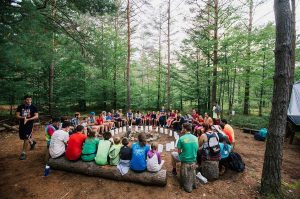Children sit in a circle in the woods at a camp