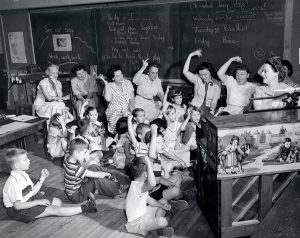 Classroom of children sitting on the floor with teachers in chairs behind them