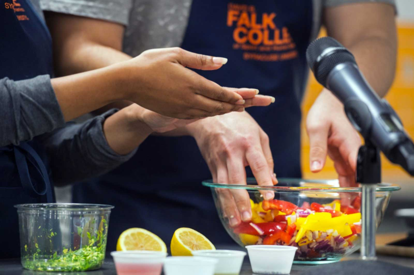 A close up of students hands working with food