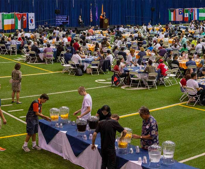 A large number of international students are sitting at tables on a stadium field