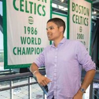 Justin Brown stand in front of a Boston Celtics sign