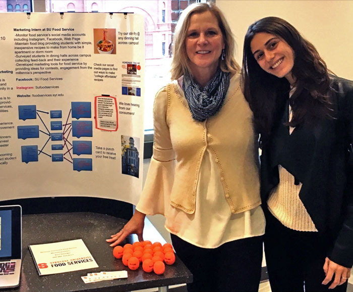 Kara Danziger poses beside her research poster on SU Food Services