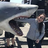 Kelly poses with her hand in a pretend shark
