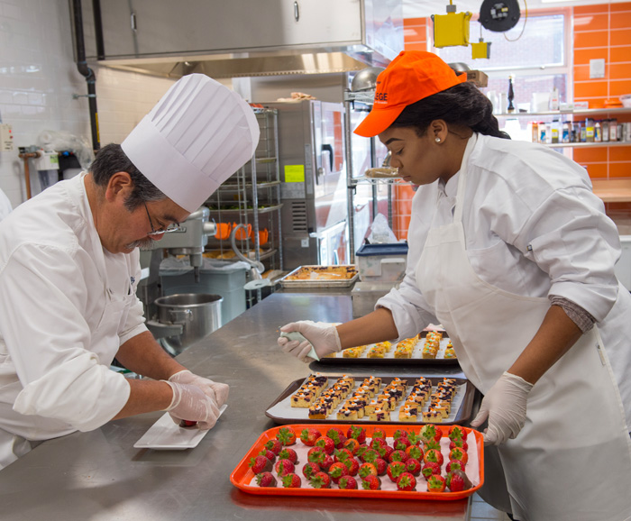 Chef Instructor Uyehara and a Falk student prepare food in Falk College's Klenk Kitchens.