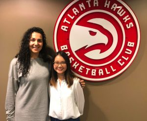 Alumna Blake Johnson with graduate student Cherie Hong standing in front of the Atlanta Hawks logo
