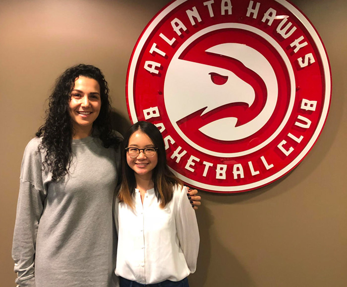 Alumna Blake Johnson with graduate student Cherie Hong standing in front of the Atlanta Hawks logo