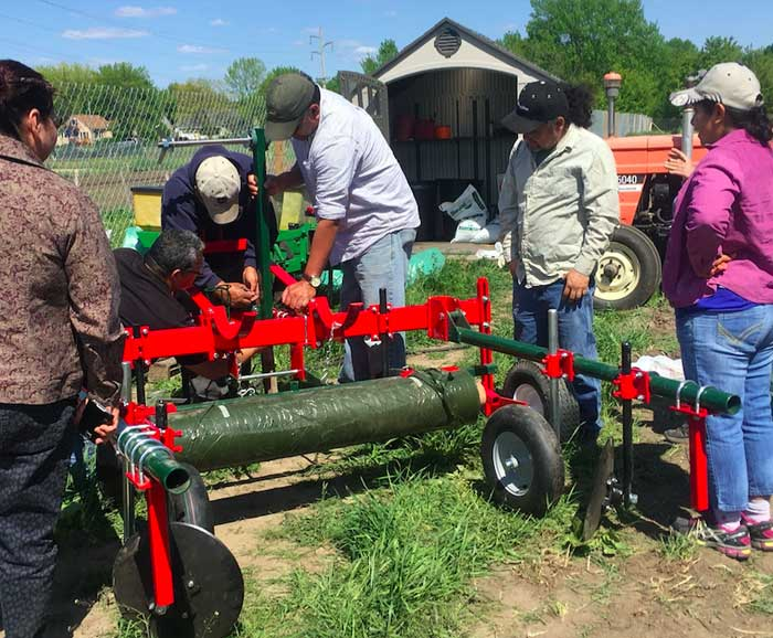 Group of farm labor workers standing around and working on a piece of farm equipment
