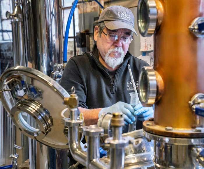 Chris Uyehara works with distilling equipment