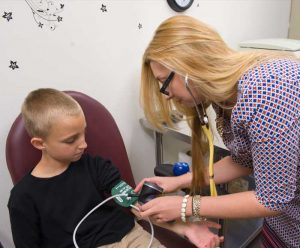 A graduate student measures the blood pressure of a child