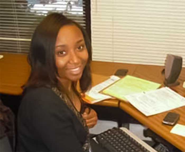 Loretta Odro sits at her desk working at her internship site