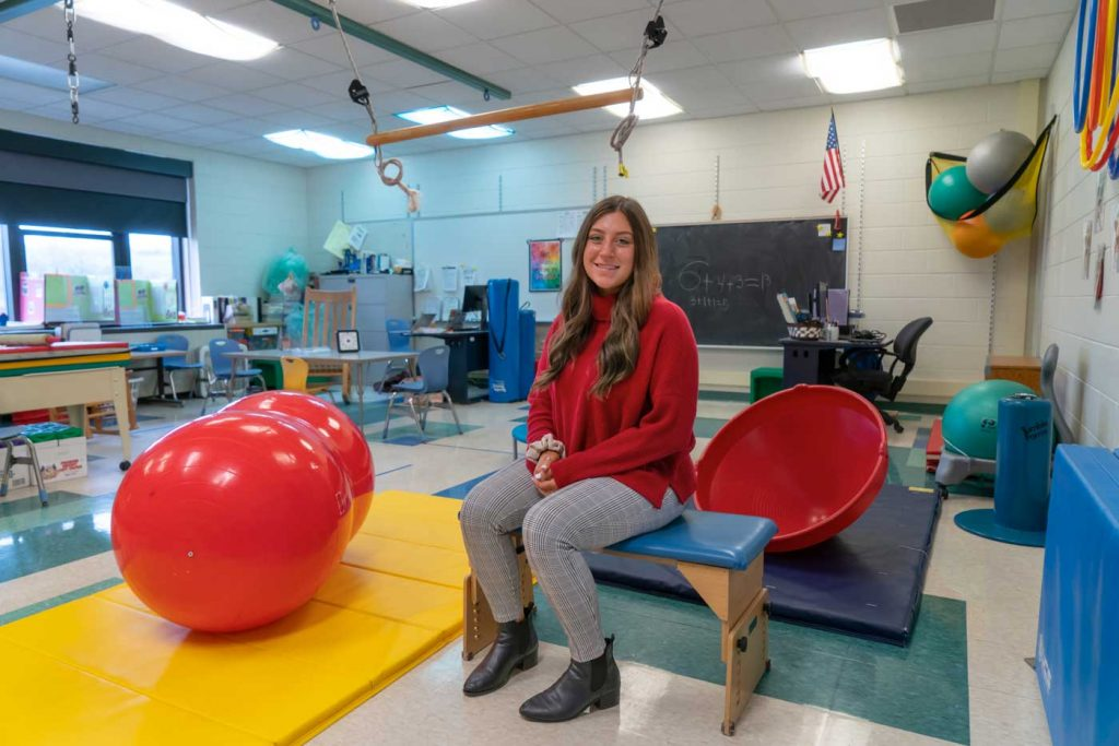 Madalyn Tallo in a room full of workout equipment for children