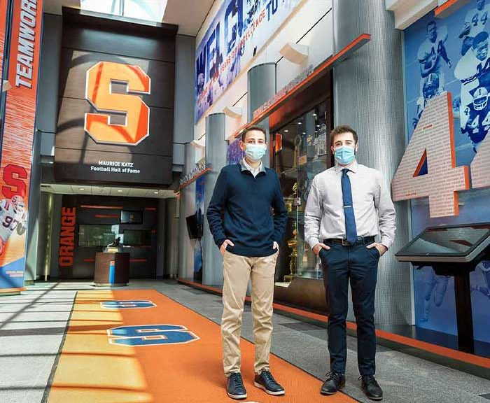 Two students stand in a sport arena lobby