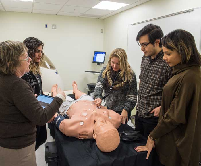 Students and professor work with a simulation mannequin