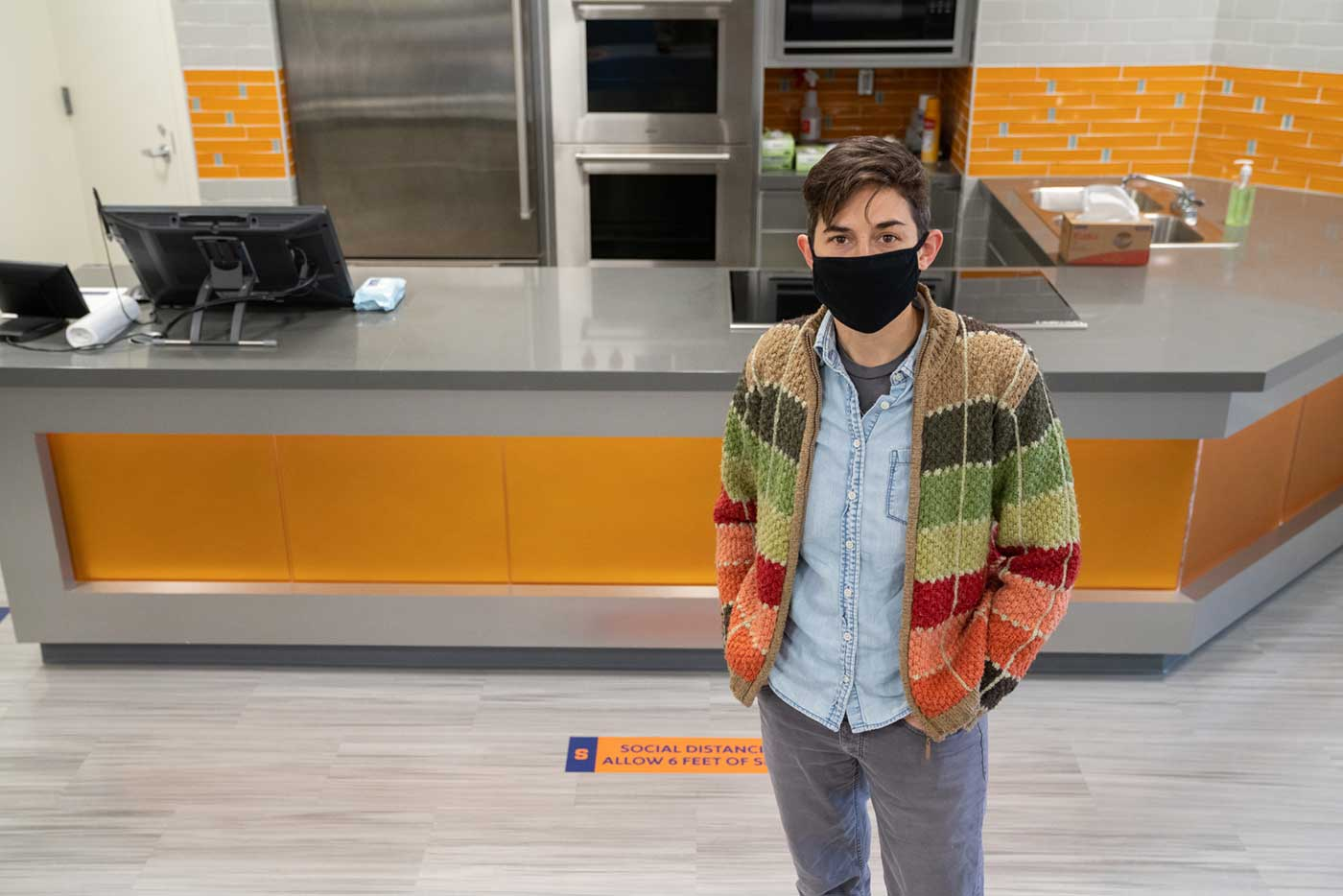 A person is standing in a studio kitchen