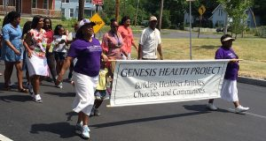 Persons walk down a road with a banner saying Genesis Health Project