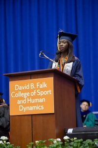 A female student presents at a podium during graduation