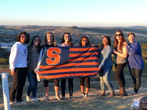 8 students are posed on a hillside holding an S.U. flag