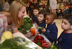 A student talks to 4 small boys about vegetables