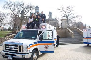 6 students pose sitting on top of an S.U. ambulance