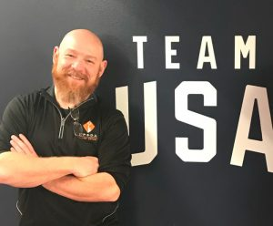 "Rob Skinner stands in front of a wall decal that reads ""Team USA"""